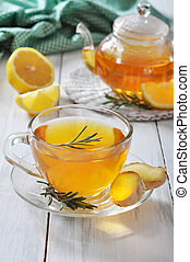 Ginger tea with lemon and rosematy in glass cup closeup.