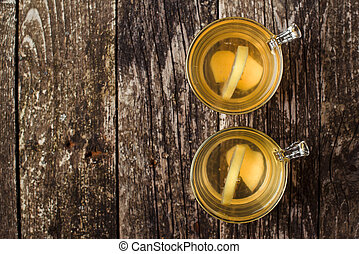 Ginger tea with lemon on the wooden background. Top view. Space for text.
