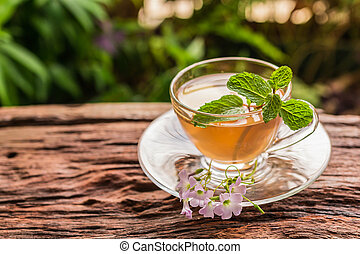 Ginger teacup with ginger slices and mint leaf on a rustic...