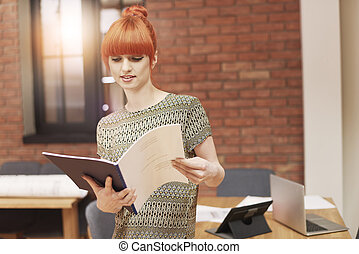 Ginger woman looking on business documents