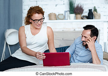 Ginger woman sitting on bed and holding laptop