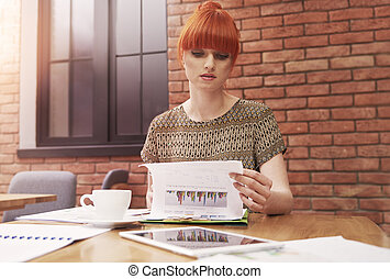 Ginger woman with stack of business documents