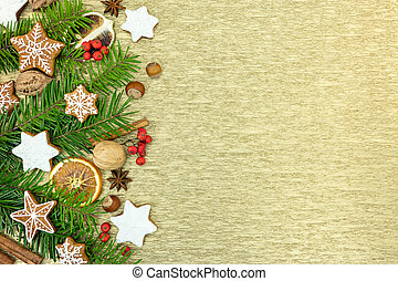 gingerbread christmas decorations with fir-tree branches on golden background