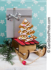 Gingerbread Christmas tree and gift on wooden sledge on a blue background