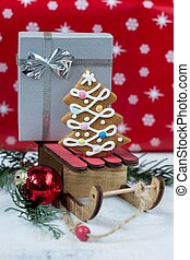 Gingerbread Christmas tree and gift on wooden sledge