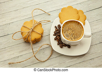 Gingerbread cookie and a cup of black coffee on a wooden background, top view