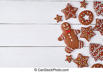 Gingerbread cookies christmas composition, with empty space for disign text on white wooden table background. New year traditional dessert food. Top view.