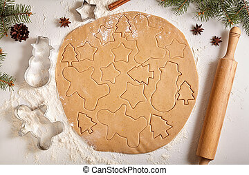 Gingerbread cookies dough preparation recipe with man shape, fir trees, snowman and star forms, cinnamon rolling pin, flour on white kitchen table. Traditional homemade christmas dessert.