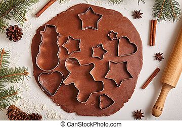 Gingerbread cookies dough preparation recipe with man shape, heart, fir trees, snowman and star forms, cinnamon rolling pin, flour on white kitchen table. Traditional homemade christmas dessert.