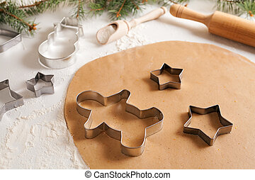 Gingerbread cookies dough with spices preparation recipe, cinnamon rolling pin and flour on white kitchen table. Traditional homemade christmas dessert.