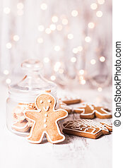 Gingerbread cookies on a table and Christmas lights on...