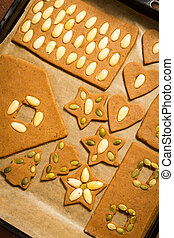 Gingerbread cookies on baking tray decorating with nuts