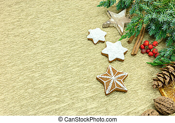 gingerbread cookies with icing as holiday decorations with spices, nuts, and fir-tree branches on gold wrapping paper