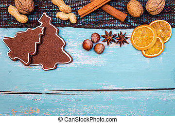 Gingerbread cookies with nuts, winter spices and orange slices on wooden table