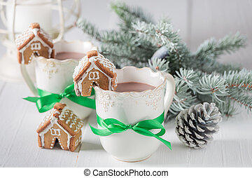 Gingerbread cottages with hot chocolate for Christmas on white table