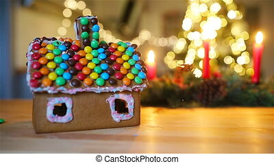 Homemade Christmas Gingerbread House on a table. Christmas tree lights in the background