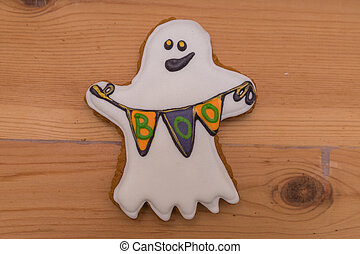 Gingerbread figure in the form of ghosts with flags lying on a wooden table. Preparing for halloween