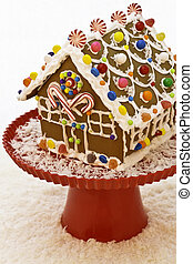 Hand made gingerbread house sitting on red cake stand decorated with assorted candies and coconut snow