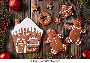 Gingerbread house, man and woman couple, stars christmas cookies with new year tree decorations frame on vintage wooden table background. Traditional homemade celebration recipe.