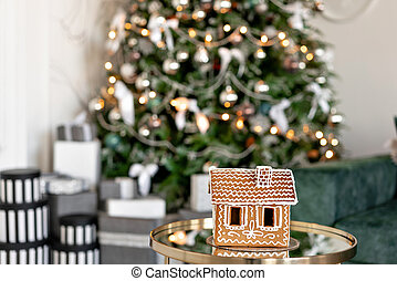 Gingerbread house on table. Defocused lights of Christmas tree. Morning in the bright living room. Holiday mood.