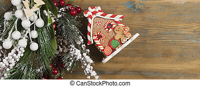 Gingerbread house with Christmas decorations on wooden background with space for your text