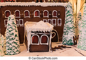 Gingerbread house with white icing and heart shaped windows with gingerbread trees