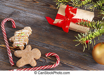 gingerbread man, cookies, lollipops, gift box with a red ribbon, spruce branch,  Golden Christmas ball on a brown wooden background