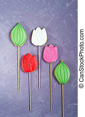 gingerbread on a stick in the form of tulips on a lilac background. Homemade holiday pastries