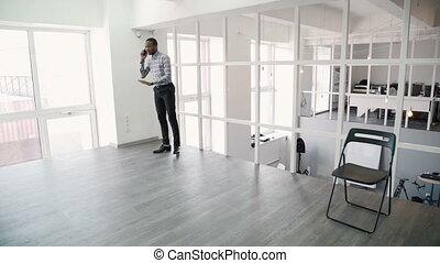 giovane, è, parlando telefono, camminare, intorno, moderno, ufficio.
