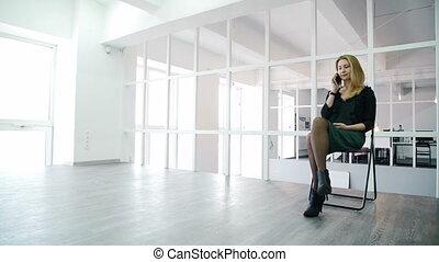 giovane, è, parlando telefono, mentre, seduta, in, moderno, ufficio.