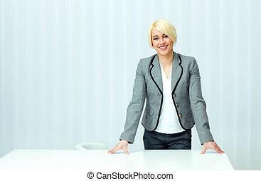 giovane, allegro, donna d'affari, in, casuale, stoffa, standing, a, lei, posto lavoro, in, ufficio
