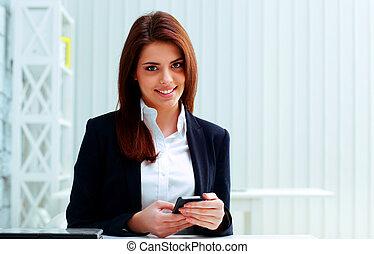 giovane, allegro, donna d'affari, presa a terra, smartphone, su, lei, posto lavoro, in, ufficio