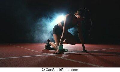 giovane, atleta, in, nero breve, e, uno, t-shirt, è, preparare, cominciare, in, il, corsa, per, 100, metri, su, il, routine, appresso, il, avvii linea