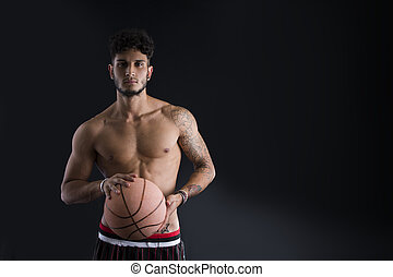 giovane, atletico, uomo, su, sfondo scuro, pallacanestro tiene, palla