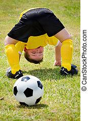 giovane bambino, osservare, palla calcio, andare, attraverso, suo, gambe, durante, organizzato, gioventù, gioco