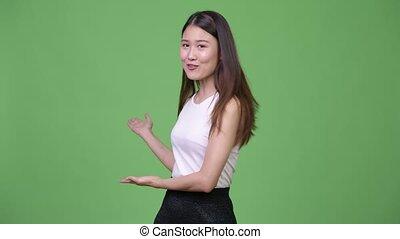 giovane, bello, asiatico, donna d'affari, presentare, qualcosa