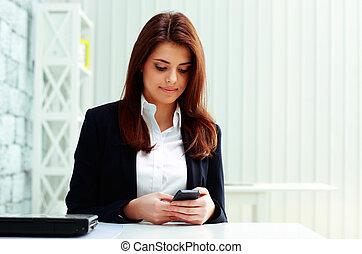 giovane, bello, donna d'affari, dattilografia, su, lei, smartphone, in, ufficio