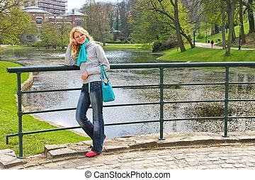 giovane, bello, ragazza, su, uno, ponte, in, uno, parco, in,...