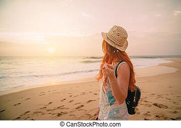giovane, camminando lungo spiaggia, a, tramonto, vista posteriore