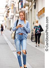 giovane, camminare, in, città, con, telefono mobile