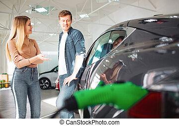 giovane coppia, acquisto, uno, primo, macchina elettrica, in, uno, showroom., discussione, circa, payment., tecnologia moderna, in, il, industria automobilistica