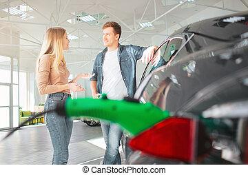 giovane coppia, acquisto, uno, primo, macchina elettrica, in, uno, showroom., ecologico, veicolo, concept., tecnologia moderna, in, il, industria automobilistica