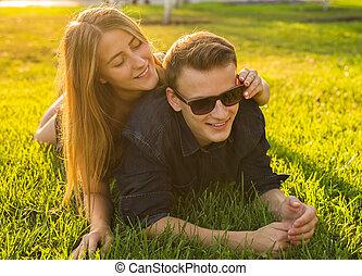 giovane coppia, divertimento, e, gioco, in, grass., donna, dire bugie, sopra, lei, amante, sorridente