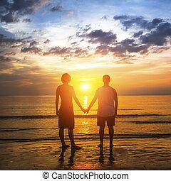 giovane coppia, durante, luna miele, su, uno, spiaggia tropicale, standing, in, il, splendore, di, un, strabiliante, sunset.
