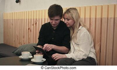 giovane coppia, in, uno, caffè, caffè bevente, e, usando, tavoletta digitale