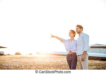 giovane coppia, insieme, durante, tramonto, standing, a, il, campo