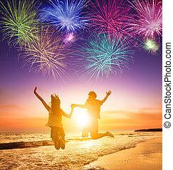 giovane coppia, saltare, spiaggia, con, fireworks, fondo