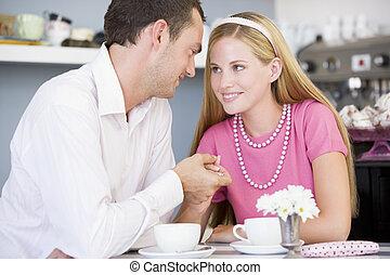 giovane coppia, sedendo ad tavola, e, detenere, tè, insieme