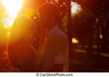 giovane coppia, silhouette, abbracciare, e, guardandolo, fuori, su, il, tramonto