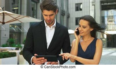 giovane, donna sorridente, parlando telefono, mentre, lei, collega, usando, tavoletta, in, il, strada.